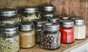 mason jars filled with spices sitting on a wood table