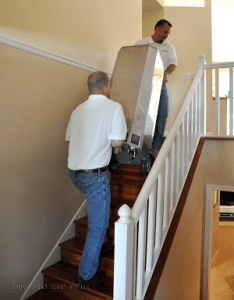 men carrying heat treatment device up stairs