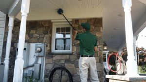 service tech green shirt spraying for pests on a porch outside