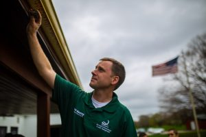 tech checking gutters for pests