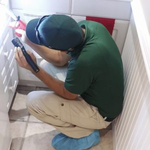 tech in green shirt crouching in a kitchen with a flashlight look for bugs in cabinets